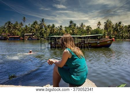 A Woman Sitting Enjoying The View Of Floating Houseboat In The Backwater Of Allepey And A Man Swimmi