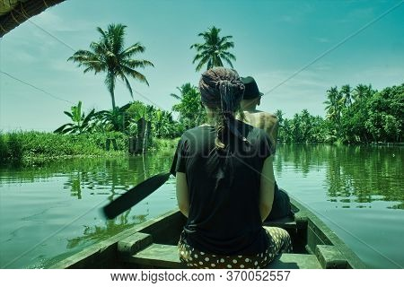 A French Man Tourist Riding A Boat Manually With A Girl In The Backwaters Of Allepey Town, Located I