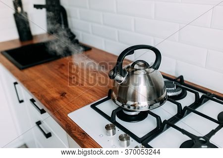 The Kettle Boils, Steam From Metal Teapot On Gas Oven. Bright Kitchen Interior. White Modern Dining