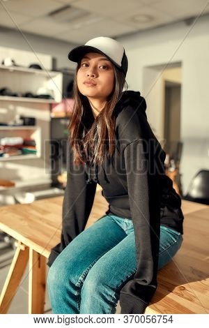 Cheerful Female Worker Looking At Camera While Posing In Custom Apparel, Baseball Cap And Hoodie. Yo