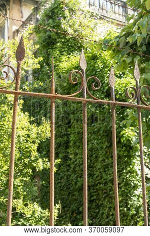 Rusty Iron Fence With Barbed Wire Fences An Abandoned House Overgrown With Plants