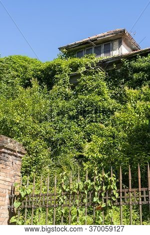 Abandoned Old House On A Hill Behind A Rusty Iron Fence With Thickets Of Plants. Vertical Dramatic L