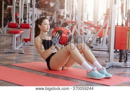 Portrait Of Fitness Woman Sitting On Yoga Mat Holding Medicine Ball And Doing Abs Exercises. Close U