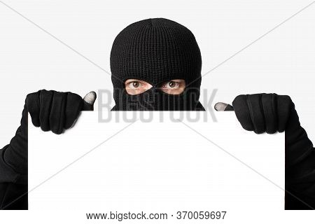Masked Gangster Holding And Looking Out White Blank Board, Isolated Over White Studio Wall