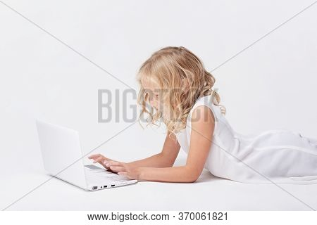 Beautiful And Cute Blonde Little Girl Plays With White Computer Notebook Laying On Floor In Bright S