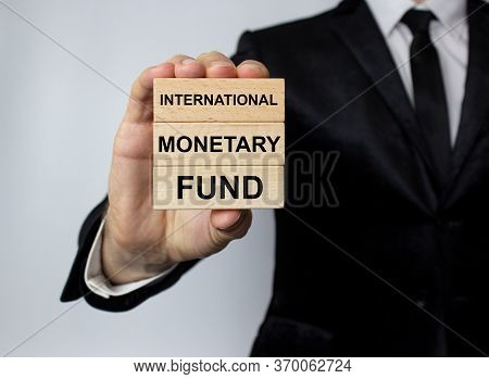 The Imf, The International Monetary Fund, Is Written On Wooden Blocks In The Hands Of A Man In A Bus