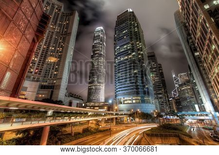 Wide Angle View Of Central Hong Kong City Skyline With Busy Roads And Streaks Of Car Lights At Night