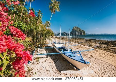 El Nido, Palawan, Philippines. Native Banca Boat And Vibrant Flowers At Las Cabanas Beach With Amazi