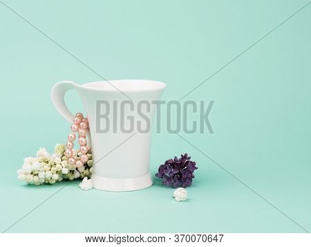 White Cup, Lilacs And Pearl Beads On Turquoise Background.