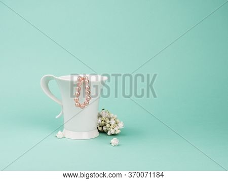 Delicate Still Life With White Cup, Lilac And Pink Pearls.