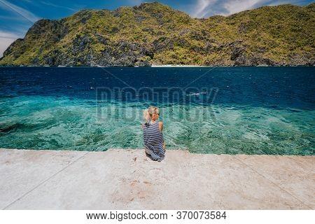Tourist Female Rear View Sitting Pier Edge On Matinloc Island On Hoping Tour C. El Nido, Palawan, Ph