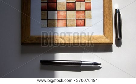 Pen On Beautiful White Fon On Warm Light. Wooden Picture Frame And Cap.