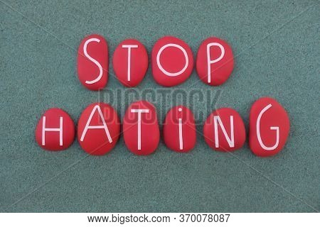 Stop Hating Slogan Composed With Red Colored Stone Letters Over Green Sand
