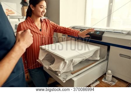Young Workers, Man And Woman Are Preparing T-shirt For Printing In The Silk Screen Printing Machine