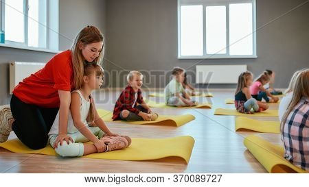 Side View Of A Little Girl Doing Butterfly Exercise With Female Trainer. Group Of Children Sitting O