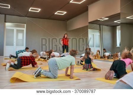 Gymnastic Exercises. Group Of Children Doing Exercises With Female Trainer In The Dance Studio. Phys