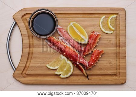 Crab Meat And Lemon On A Wooden Chopping Board Next To Soy . Delicious Seafood. The Food For Gourmet