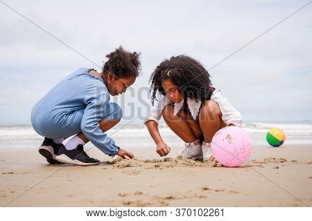 Happy Friendship. Happy Vacation Holiday. Happy Two African American Kids Are Building A Sandcastle