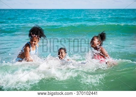 Happy Three African American Kids Are Swimming In The Sea Playfully Together. With Waves And Splashe
