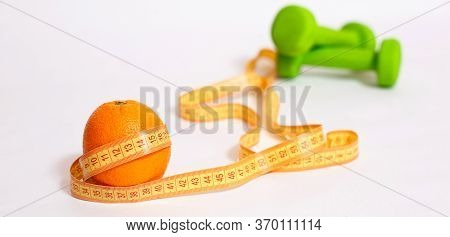 Orange, Centimeter Tape, Green Dumbbells On A White Background With Space For Text. The Concept Of L