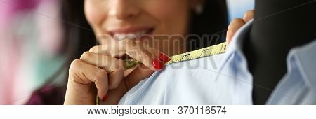 Woman Applies Measuring Tape To Shoulder Seam. Tailor Smiles And Takes Necessary Measurements To Mak