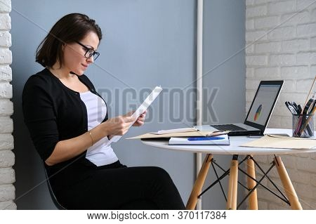 Mature Woman Working In Home Office, Female Sitting At Desk With Laptop Reading Business Finances Pa
