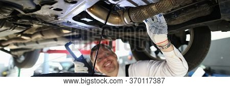 Mechanic Conducts Thorough Inspection Car Garage. Male Mechanic In Working Overall Stands Under Car