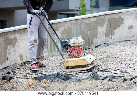 A Construction Worker Compacts Crushed Stone With A Petrol Vibratory Compactor.