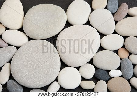 Top View Of Arranged Pebble Stones On Black Background