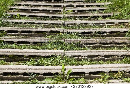 Homemade Stairs Made Of Concrete Slabs With Hollow Inside, Closeup, Green Grass Grows Between The Sl