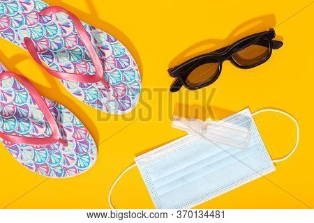 Flat Lay Composition With Summer Vacation Accessories And Face Mask On Yellow Background. Summer Or