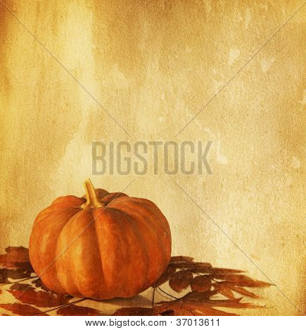 old paper with pumpkin and dry autumn leaves