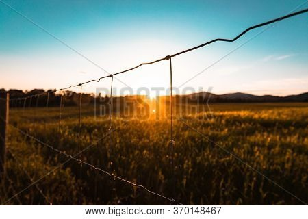 Sunset Over Wheat Field Seen Through A Wire Fence With Copy Space