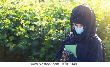 Oriental Woman In A Protective Medical Mask Quaran In Her Hands. A Migrant From The In A Mask On Her