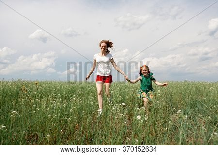Mom and daughter run across the field
