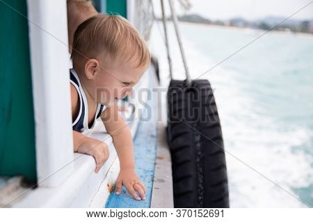 Little boy looks out of the window of a boat