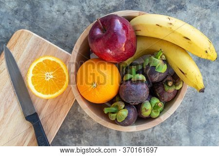 Cutting Orange On Wooden Board With Multi Fruit In Wooden Bowl Frome Top View.