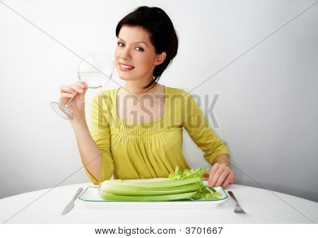 Young Woman Having Her Breakfast With Water And Celery