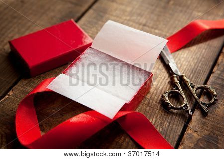 Opening or preparing a gift in a red box.  A red gift box, scissors, and a red ribbon. Focus is in the center of the gift box.