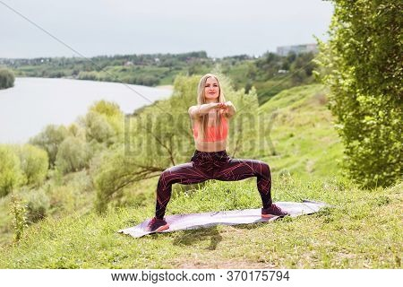 Fitness Instructor Is Doing Plie Squats On The River Bank Outdoors. Summertime.