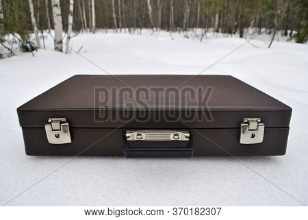 The Closed Briefcase Is Lying On The Snow. Brown Briefcase Close-up.