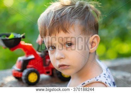 Little boy plays typewriter in the yard