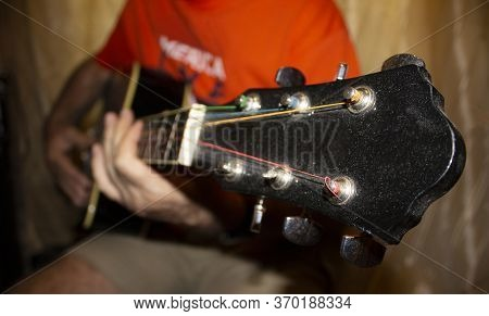 The Fretboard Of An Old Acoustic Guitar And Fingers On Strings. Selective Focus