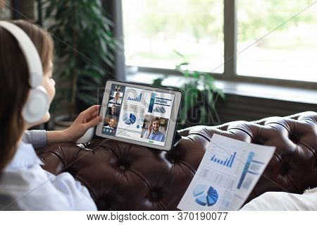 Business Woman In Headphones Lying On Sofa Speak Talking To Her Colleagues In Video Conference. Busi