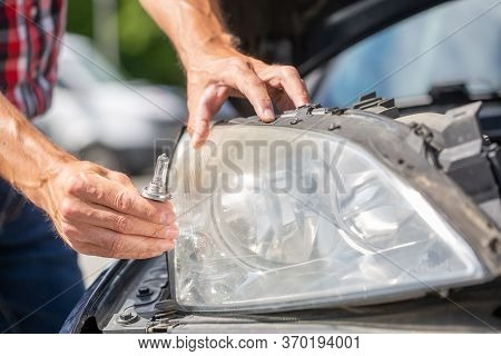 Young Man Hands Changing Car Bulb Or Flashbulb Of The Front Headlight Or Headlamp, Repairing Car Con