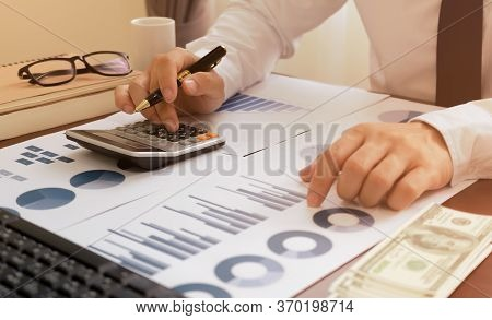 Bookkeeper Or Financial Inspector Using A Calculator To Calculate Report Profit, Analyzer Graph Bala