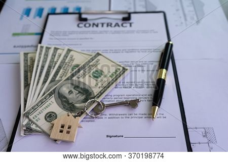 House Key With House Shaped Keyring , Money, And Pen On Contract Of House Purchase Agreement Near Th