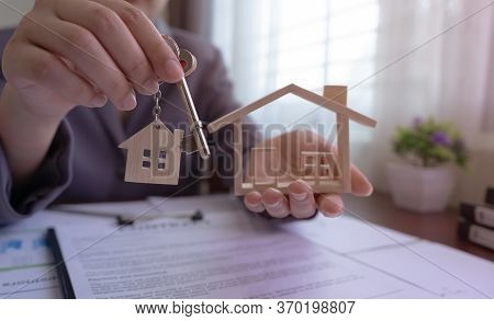 Close Up. Real Estate Agent Holding House Key And House Model On Table With House Designs Document,