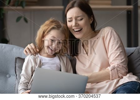 Overjoyed Mom And Little Daughter Using Laptop Together