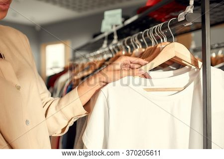 Cropped Shot Of Woman Looking At Already Made Items In The Store. Choosing Clothes At Custom T-shirt